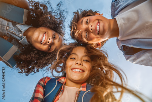 Portrait of smiling school kids standing in cecrle at school yard with look in c Canvas Print