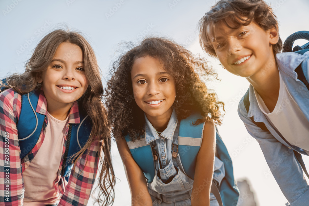 Fototapeta Portrait of school childrens smiling and looking in camera outdoors