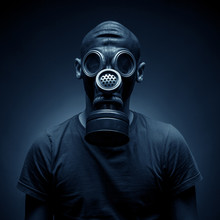 Young Man In A Gas Mask Against A Dark Background