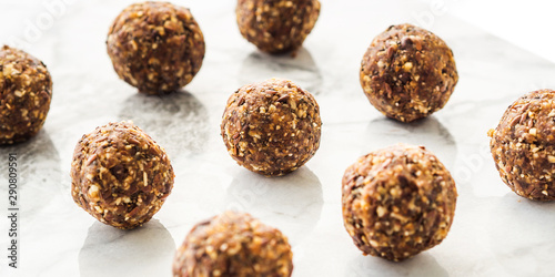 fototapeta na lodówkę Energy protein balls with healthy ingredients on marble table. Home made with dates, peanut butter, flax and chia seeds, oats, almond and chocolate drops. Food modern pattern on marble table