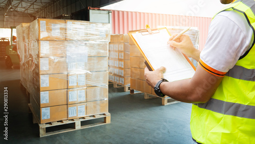Fotomural  warehouse worker hand holding clipboard inspecting checklist details of cargo shipment, goods pallets for loading with a truck container at dock warehouse
