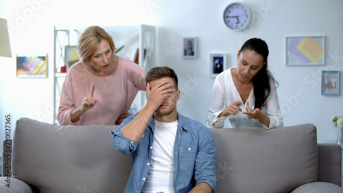 Fotografia Tired man sitting on sofa, enduring to wife and mother criticize him, quarrel