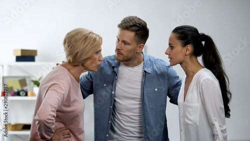 Man trying to calm wife and mother arguing, in-law conflict, troubled marriage Wallpaper Mural