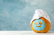 Leinwandbild Motiv Pumpkin with facial mask and towel on wooden background, copy space