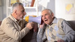 canvas print picture - Senior man shouting bullhorn to deaf friend, old aged health, deafness treatment