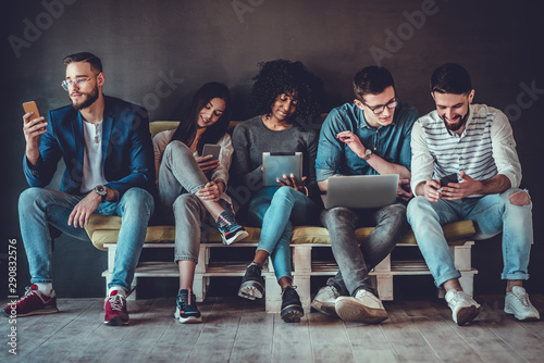 Fotografía  Group of happy young people sitting on sofa and using digital tablet and laptop