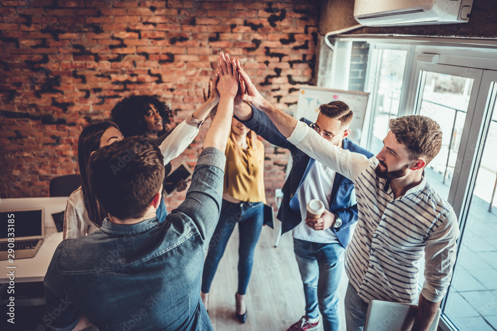 Fototapeta Successful team of young professionals celebrating achievement in work project giving high-five to each other in office