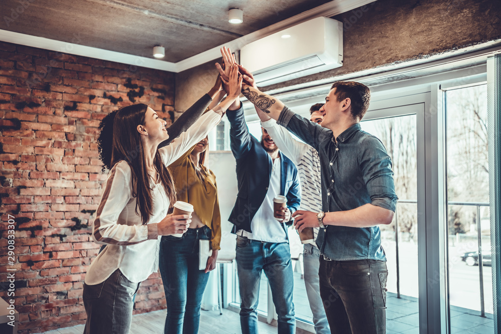 Fototapety, obrazy: Successful business team is giving high five and smiling while standing in office
