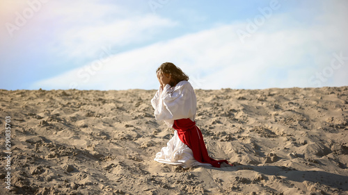 Photo Man in robe repenting for sins, praying to God in desert, pangs of conscience