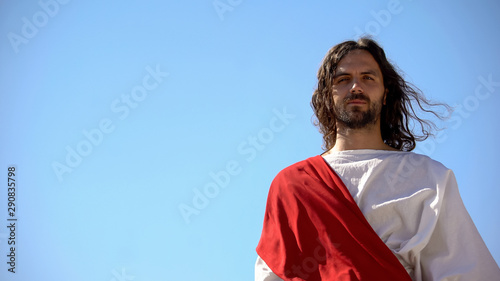 Historical personification of Jesus Christ looking after people against blue sky Canvas Print