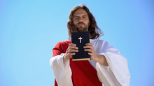 Strict God Holding Bible Against Blue Sky, Reminding Of Faith And Repentance