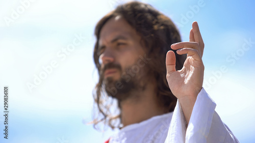 Preacher showing blessing sign against blue sky, hand of benediction, baptism Wallpaper Mural