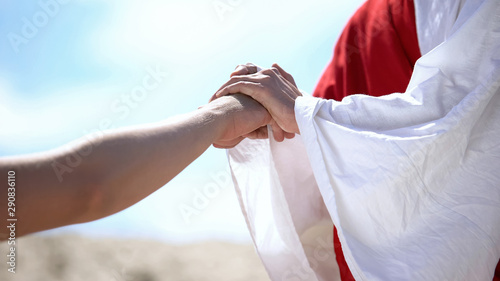 Tela Jesus holding male hand to bless and heal Christian, religious miracle, closeup