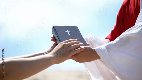 Preacher in robe passing bible to male hands, spreading religious teachings Canvas Print