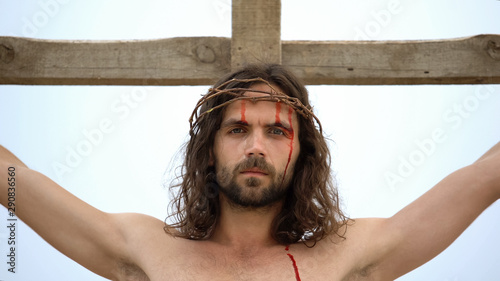 Exhausted Jesus nailed to cross, looking into camera, atoning humanity sins Wallpaper Mural