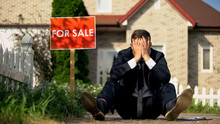 Extremely Upset Real Estate Manager Sitting By For Sale Signboard, Failed Deal