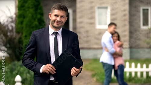 Smiling broker standing with documents, happy family hugging near their new home Fototapete