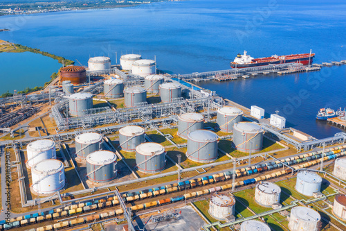 Fototapeta Aerial view of large fuel storage tanks at oil refinery industrial zone in the cargo seaport, and ship tanker at unloading. obraz