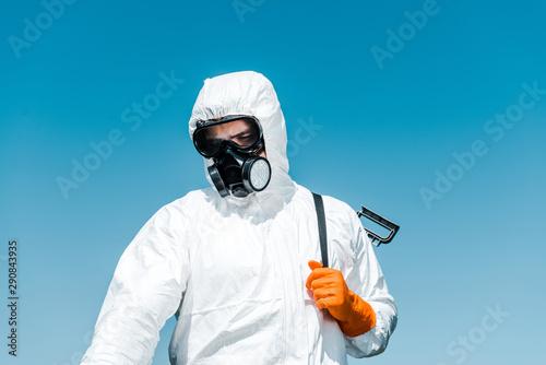 Fotografia  exterminator in white uniform and latex glove holding spray