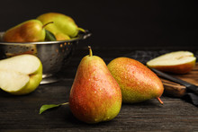 Ripe Juicy Pears On Dark Wooden Table Against Black Background