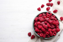 Bowl With Delicious Ripe Raspberries On White Wooden Table, Top View. Space For Text