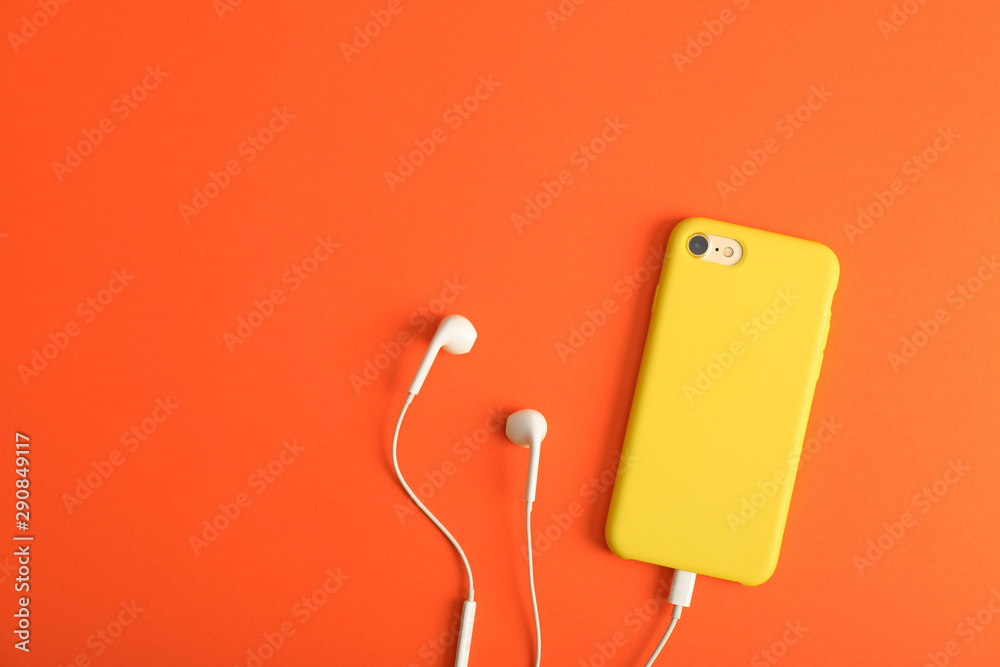 Fototapeta Modern phone with earphones on coral background, top view. Space for text