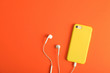 canvas print picture - Modern phone with earphones on coral background, top view. Space for text