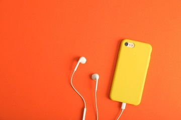 Modern phone with earphones on coral background, top view. Space for text
