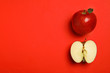 canvas print picture - Flat lay composition with ripe juicy apples on red background, space for text