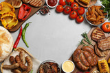 Frame of barbecued meat and vegetables on light table, flat lay. Space for text