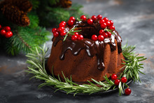 Christmas Chocolate Bundt Cake With Glaze Decorated With Fresh Berries And Rosemary. Winter Baking At Xmas Or New Year With Decorations On Dark Background