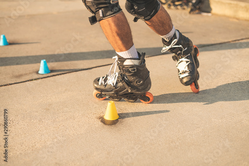 Fotografía  Close-up view of the rollers of a caucasian man, doing rollerblading, inline skating, performing on a slalom course on asphalt surface