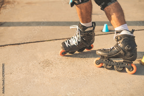 Fotomural  Close-up view of the rollers of a caucasian man, doing rollerblading, inline skating, performing on a slalom course on asphalt surface