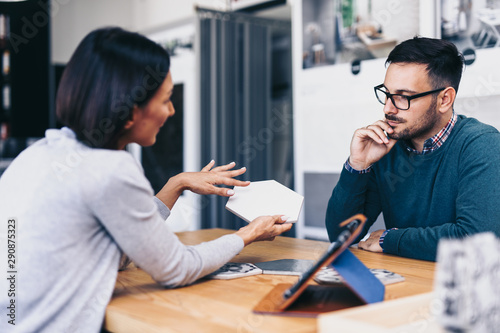 Middle age man choosing ceramic tiles and utensils for his home bathroom and female seller helps him to make right decision