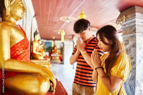 thai couple praying in front of buddha statue at Wat Phrathat Doi Suthep temple Tableau sur Toile