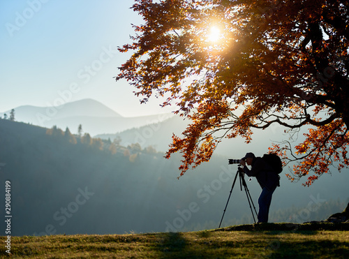 Photo sur Aluminium Bleu ciel Hiker photographer taking picture of misty mountain landscape using camera on tripod on quiet autumn evening, standing on grassy valley under large tree with golden leaves under blue sky at sunset.