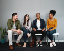 Diverse Group Of Friends Sitting On Chair Waiting In Queue Smiling And Enjoying Together - Young Group Of Friends Experiencing A Sense Of Belonging And Inclusion And Connection