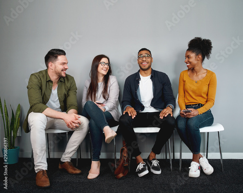 Obraz na plátně Diverse group of friends sitting on chair waiting in queue smiling and enjoying