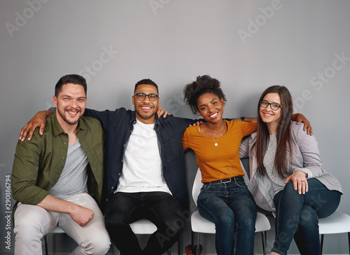 Cuadros en Lienzo  Portrait of multiethnic young friends sitting together happily with their arms a