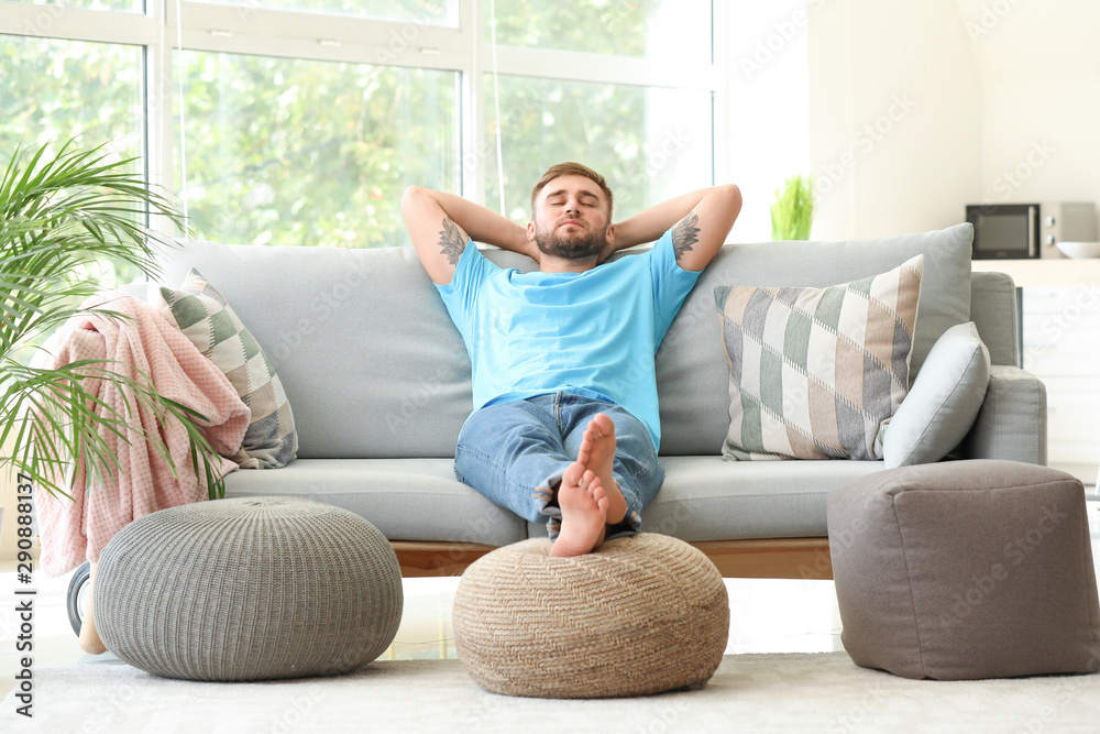 Fototapeta Handsome young man relaxing at home