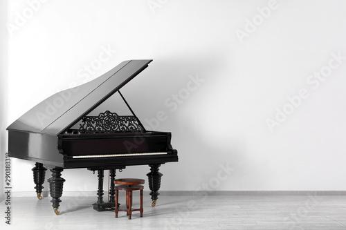 Fotografía  Black grand piano near white wall in empty room