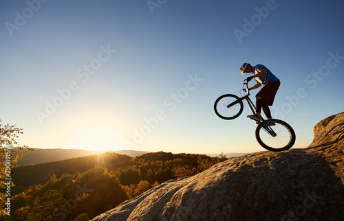 Silhouette of cyclist balancing on back wheel on trial bicycle Canvas Print