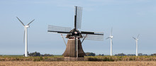 Old Windmill And Modern Turbines Together In Agricultutre Landscape Of Friesland
