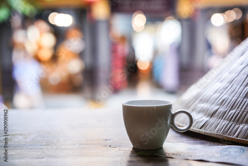 Photo Stands Cafe Empty tall transparent glass of macchiato or capuccino coffee with small white syrup mug and Vietnam money banknote and Vietnamese straw hat with traditional hat in coffee. Shop as background