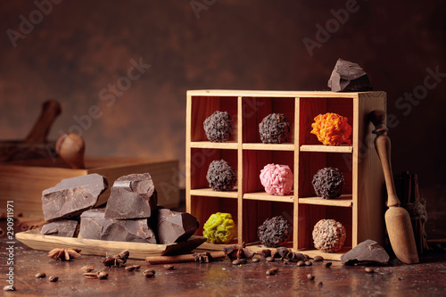 Chocolate candy in wooden box, broken pieces of chocolate, cinnamon sticks, anise and coffee beans.