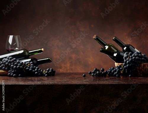 Photo sur Toile Amsterdam Juicy blue grapes and bottles of red wine on a brown background.