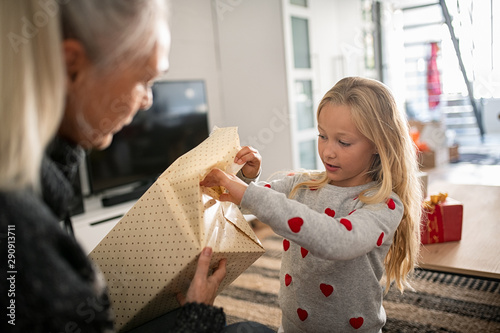 Valokuva  Girl unwrapping present for birthday