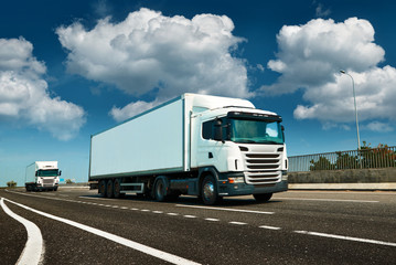 White truck is on highway - business, commercial, cargo transportation concept, clear and blank space on the side view