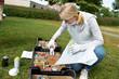 canvas print picture - junge Teilnehmerin beim Graffiti Workshop bedient sich an der Box mit Spraydosen