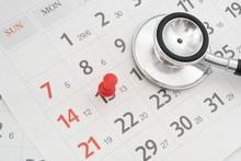 Regular Medical Examination Concept, Black Stethoscope And Push Pin On Calendar Background